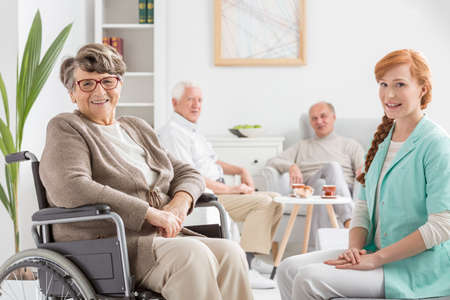 common room: Senior on a wheelchair with young nurse
