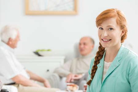 common room: Senior men talking behind the young nurse