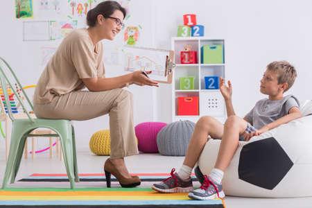 Menino sentado no moderno parafuso de futebol durante a sessão com o psicólogo