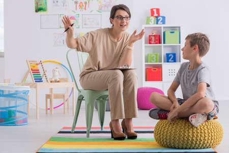terapia psicologica: consejero escolar positivo y el alumno sentado en el aula de luz