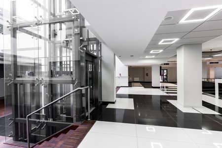 障害のある学生の大学建物エレベーターでモダンな廊下のショット