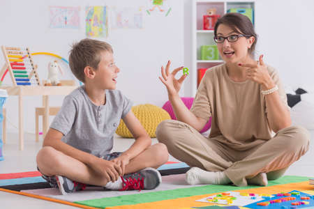 Young private tutor teaching child, sitting on floor together Stock Photo