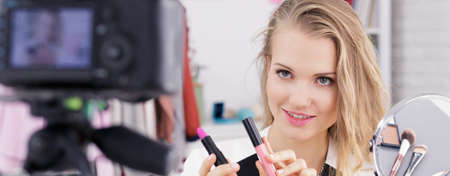 Pretty blogging teenager showing lipsticks on her make up video