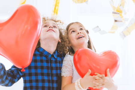 carelessness: Cute child couple with red balloon hearts Stock Photo