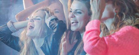Grupo de chicas bailando durante la fiesta ruidosa Foto de archivo