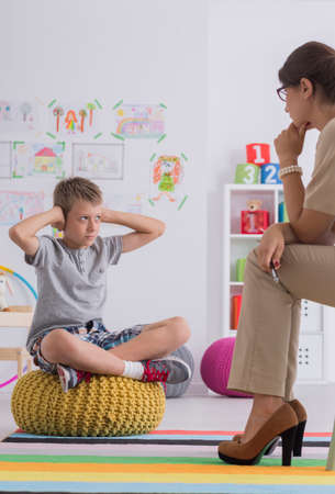 Misbehaved boy covering his ears while talking with psychotherapist