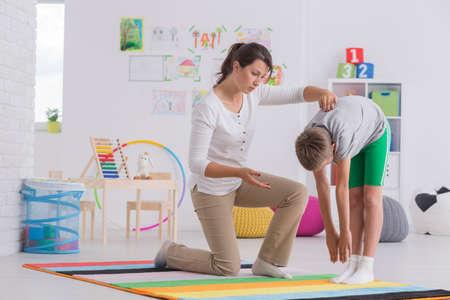 Niño de pie se inclina hacia adelante durante el ejercicio con el fisioterapeuta Foto de archivo - 69988673
