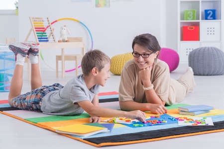 교사와 함께 바닥에 누워있는 아이, 학습