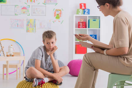 Bored child sitting on pouf while having conersation with psychotherapist