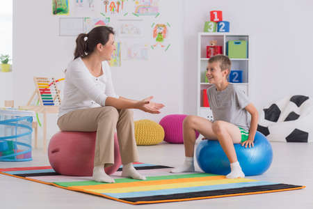 gym ball: Young physiotherapist and smiling boy sitting on gym ball