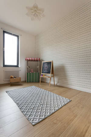 juguetes de madera: Spacious babys room with wooden floor and white walls. In the corner cradle and kids toys