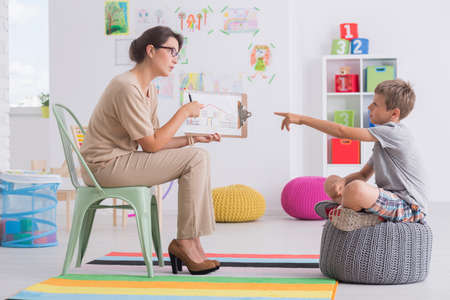 Young woman holding a picture conducting childs psychological test Stock Photo