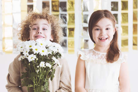 Boy with bouquet of white flowers and cute small girl