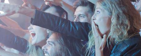 彼らのお気に入りのバンドのコンサートを楽しんでいる若者