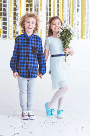 Adorable child couple, girl holding bouquet of flowers