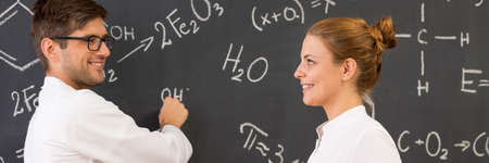 successfull: Smiling young students in uniforms writing chemistry formulas on blackboard at university Stock Photo