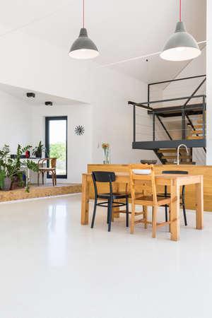 appartamento bianco piano aperto con zona pranzo, cucina isola, scale e l'ufficio domestico aperto Archivio Fotografico