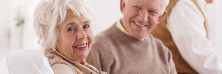 happy senior: Happy senior couple smiling and sitting on a sofa Stock Photo