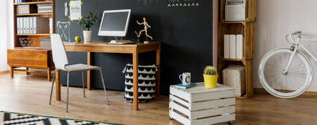 furniture home: Artistic hipster flat with a bike, DIY table, desk, chair, computer, bookcase and blackboard wall, panorama Stock Photo
