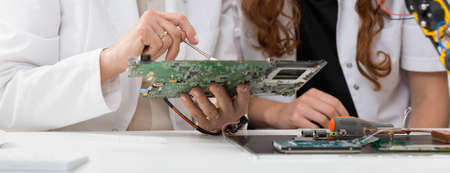 Woman students analyzing computer components in technology university
