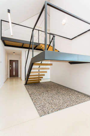 Interni bianchi e spaziosi con scale a soppalco, soppalco, porta d'ingresso sullo sfondo Archivio Fotografico - 70023347