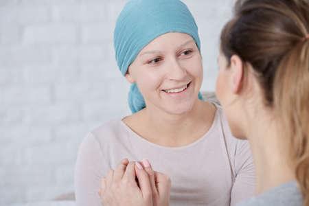 家族のサポートを持つスカーフを身に着けている脳腫瘍を持つ女性