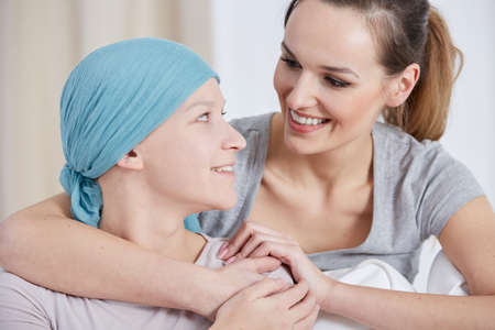 Hopeful cancer woman wearing headscarf, talking with friend Stok Fotoğraf