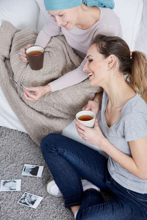 Camcer woman drinking tea and watching family pictures with sister