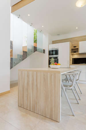 lacquered: White modern lacquered kitchen design with wooden countertop and glass staircase Stock Photo
