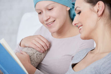 Ill woman wearing headscarf, reading book with friend