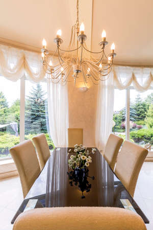lightsome: Elegant dining room with big table, chairs and chandelier Stock Photo