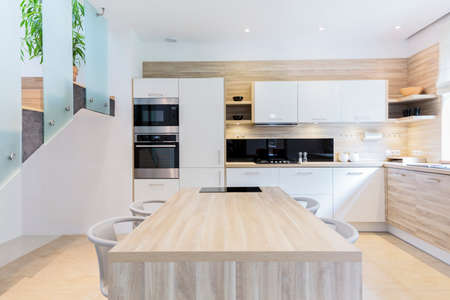 lacquered: Bright fitted modern kitchen project in light colors with wooden furnitures Stock Photo