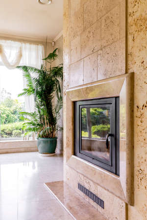 lightsome: View of a travertine wall with fireplace next to big window with curtains