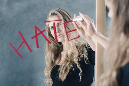 Teenager with self confidence problem and hate to herself looking in the mirror
