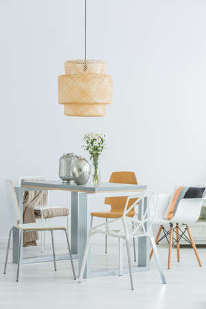 communal: White room with functional communal table, chairs and ceiling lamp Stock Photo