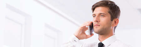 Handsome young man in white shirt and dark tie with mobile phone Stock Photo