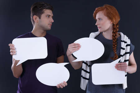 Young couple holding blank speech bubbles, dark background