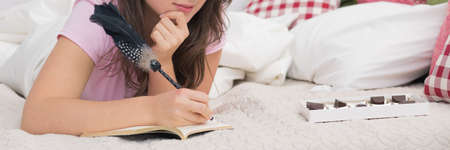 diaries: Young woman lying in bed and writing diary