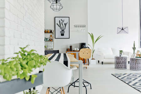 Well-lighted dining area of modern and sapcious loft