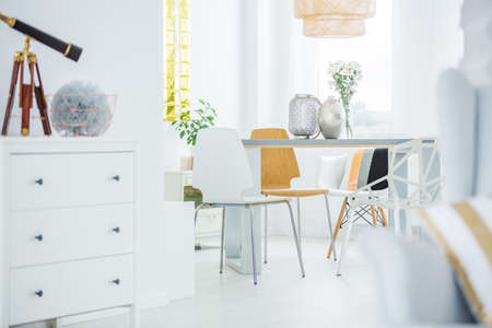 White room with dresser, communal table and chairs