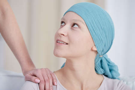 Young woman after chemotherapy smiling, wearing headscarf