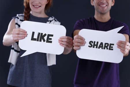 Couple holding word balloons with like and share text
