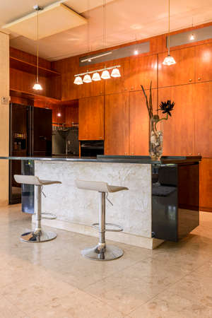 fridge lamp: Stone kitchen island with two bar stools and wooden accents in kitchen Stock Photo