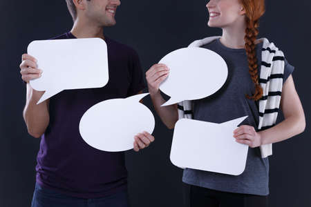 interpersonal: Man and woman holding blank speech bubbles Stock Photo