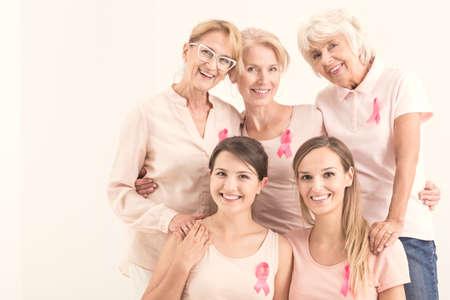 Happy multigeneratinal women with pink ribbons in anticancer campaign Foto de archivo
