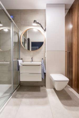 round: Grey bathroom with toilet, basin and round mirror Stock Photo