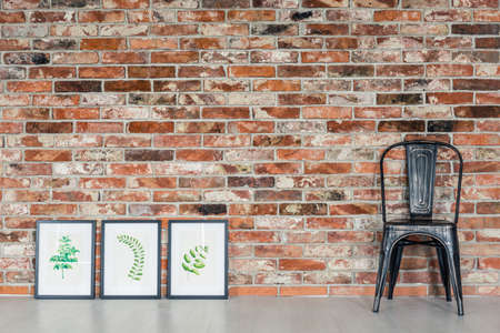 living style: Loft interior with leaves paintings, black chair Stock Photo