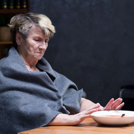Depressed elderly woman refusing to eat healthy meal