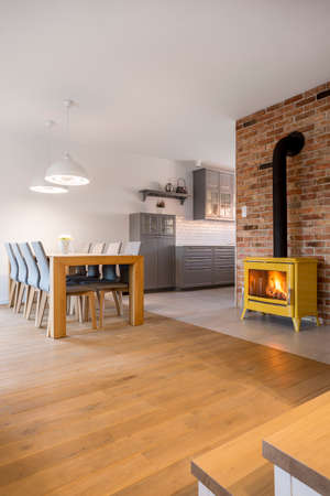 upholstered: Apartment with dining area, fireplace, stairs and open kitchen