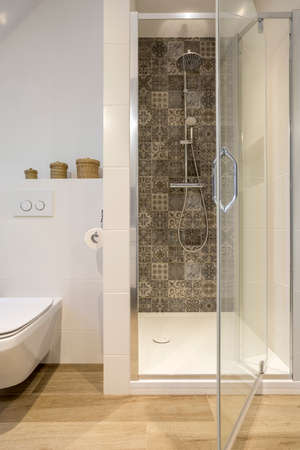 wood flooring: White bathroom with shower, toilet and wood effect flooring Stock Photo